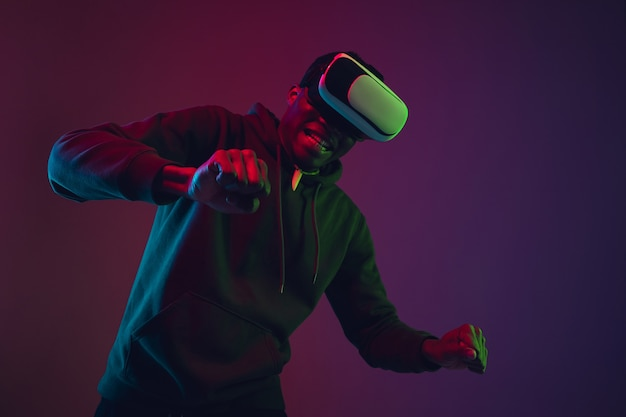 African-american man's portrait in vr-headset isolated on gradient studio background in neon light. beautiful male model. concept of human emotions, facial expression, sales, ad, inclusion, tech.
