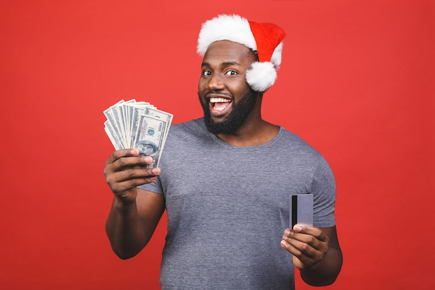 African american man in santa hat holding credit card and money