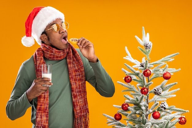 Uomo afroamericano in cappello della santa e sciarpa intorno al collo che mangia biscotto che tiene il bicchiere di latte in piedi accanto a un albero di natale su sfondo arancione