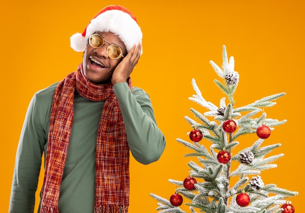 Uomo afroamericano in cappello della santa e sciarpa intorno al collo felice e positivo che osserva da parte in piedi accanto a un albero di natale sopra la parete arancione