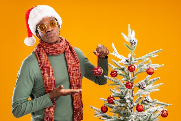 Uomo afroamericano in cappello della santa e sciarpa intorno alla sfera della tenuta del collo che lo presenta guardando dispiaciuto in piedi accanto a un albero di natale su sfondo arancione
