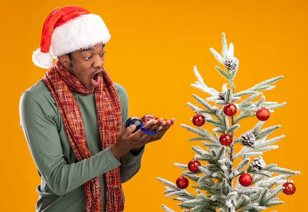 Uomo afroamericano in cappello della santa e sciarpa intorno al collo che tiene le palle di natale guardandoli stupito in piedi accanto a un albero di natale su sfondo arancione