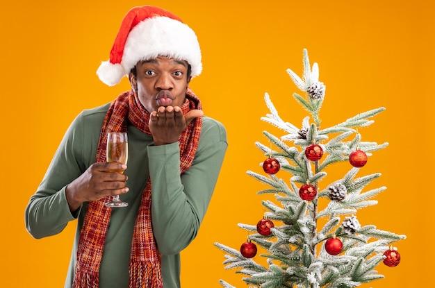 Uomo afroamericano in cappello da babbo natale e sciarpa intorno al collo che tiene un bicchiere di champagne che soffia un bacio con il braccio davanti al viso in piedi accanto a un albero di natale su sfondo arancione