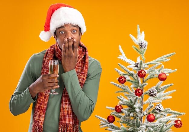 Uomo afroamericano in santa cappello e sciarpa intorno al collo tenendo un bicchiere di champagne guardando la telecamera scioccato che copre la bocca con la mano accanto all'albero di natale su sfondo arancione