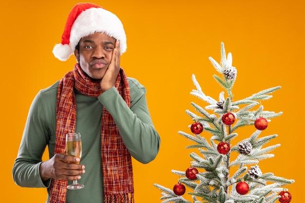 Uomo afroamericano in santa cappello e sciarpa intorno al collo tenendo un bicchiere di champagne guardando la telecamera stanco e annoiato accanto all'albero di natale su sfondo arancione