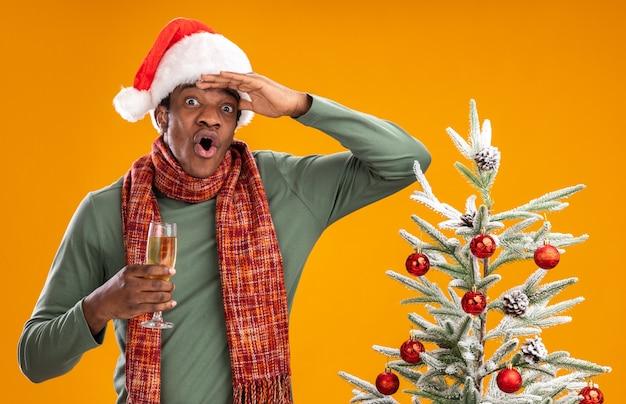 Uomo afroamericano in cappello da babbo natale e sciarpa intorno al collo che tiene un bicchiere di champagne guardando lontano sorpreso con la mano sopra la testa in piedi accanto a un albero di natale su sfondo arancione