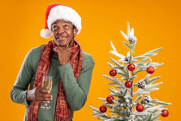 Uomo afroamericano in cappello della santa e sciarpa intorno al collo che tiene un bicchiere di champagne guardando perplesso accanto all'albero di natale su sfondo arancione