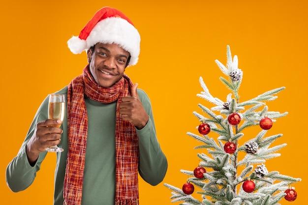 Uomo afroamericano in santa cappello e sciarpa intorno al collo tenendo un bicchiere di champagne sorridendo allegramente mostrando pollice in alto accanto all'albero di natale su sfondo arancione