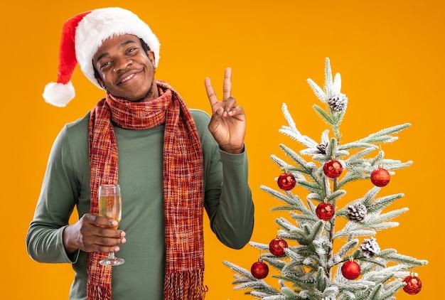 Uomo afroamericano in santa cappello e sciarpa intorno al collo tenendo un bicchiere di champagne sorridendo allegramente mostrando v-segno accanto all'albero di natale su sfondo arancione
