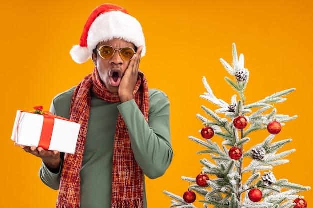 Uomo afroamericano in santa cappello e sciarpa intorno al collo tenendo un presente guardando la telecamera stupito e sorpreso in piedi accanto a un albero di natale su sfondo arancione