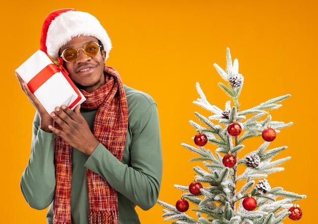 Uomo afroamericano in santa cappello e sciarpa intorno al collo tenendo un presente guardando la fotocamera con il sorriso sul viso in piedi accanto a un albero di natale su sfondo arancione