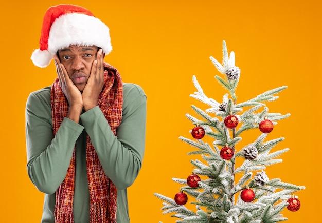 Uomo afroamericano in santa cappello e sciarpa intorno al collo guardando la telecamera infastidito e preoccupato in piedi accanto a un albero di natale su sfondo arancione