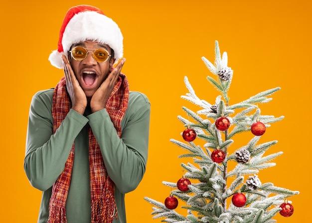 Uomo afroamericano in cappello della santa e sciarpa intorno al collo che guarda l'obbiettivo felice ed eccitato in piedi accanto a un albero di natale su sfondo arancione