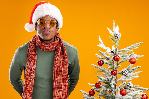 African american man in santa hat and scarf around neck looking at camera keeping lips like going to kiss standing next to a christmas tree over orange background