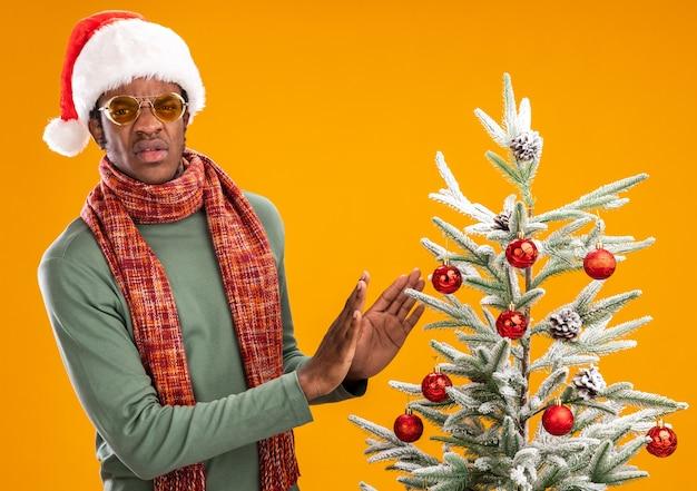 Uomo afroamericano in cappello della santa e sciarpa intorno al collo che sembra scontento che fa gesto di difesa in piedi accanto a un albero di natale su sfondo arancione