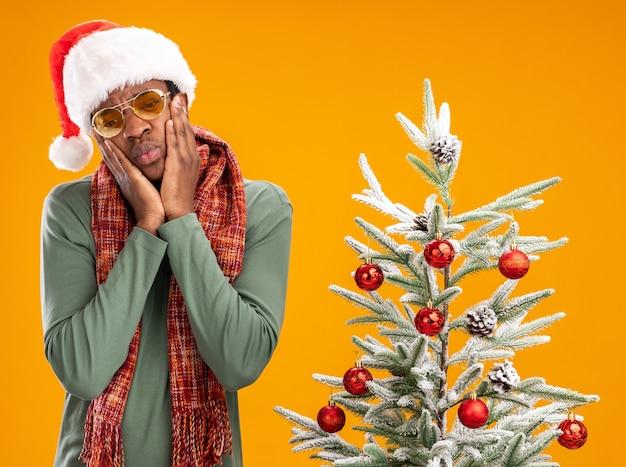 Uomo afroamericano con cappello da babbo natale e sciarpa intorno al collo guardando in basso con espressione triste in piedi accanto a un albero di natale su sfondo arancione orange