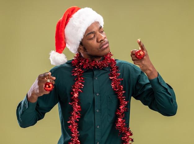 Uomo afroamericano in cappello della santa con la ghirlanda che tiene le palle di natale guardando la palla con il viso serio in piedi su sfondo verde