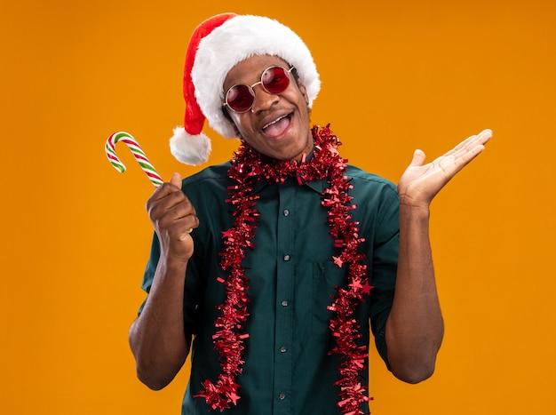 Uomo afroamericano in cappello della santa con la ghirlanda che indossa gli occhiali che tengono il bastoncino di zucchero felice ed eccitato in piedi sopra la parete arancione