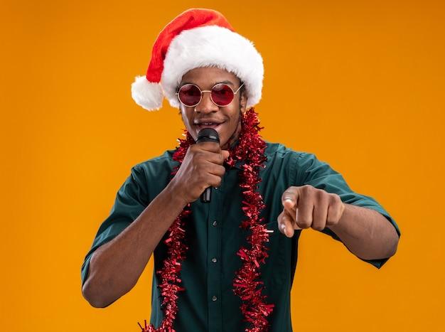 Uomo afroamericano in cappello della santa con la ghirlanda con gli occhiali che tiene il microfono che canta in piedi felice e positivo sopra fondo arancio