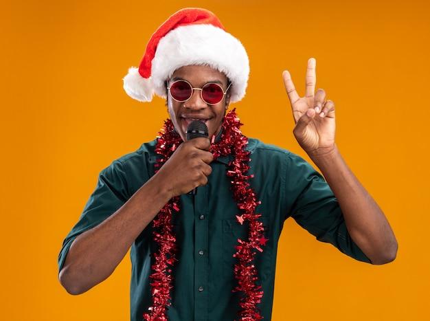 Uomo afroamericano in cappello della santa con la ghirlanda con gli occhiali che tiene il microfono sorridente che mostra il segno di v che sta sopra la parete arancione
