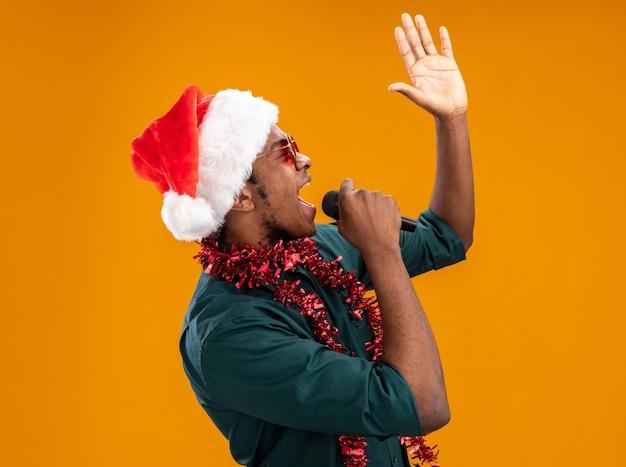 Uomo afroamericano in cappello della santa con la ghirlanda con gli occhiali che grida al microfono con il braccio alzato che sta sopra fondo arancio