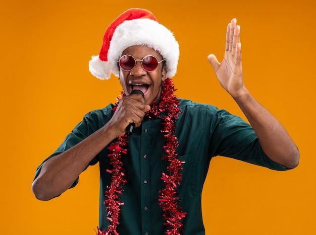 Uomo afroamericano in cappello della santa con la ghirlanda con gli occhiali che grida al microfono con il braccio alzato che sta sopra la parete arancione