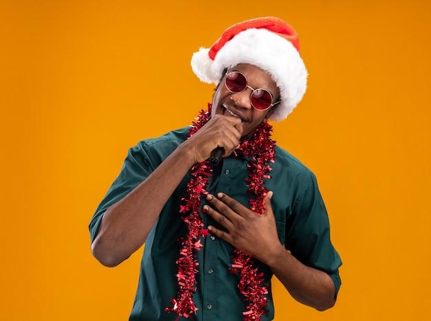 Uomo afroamericano in cappello della santa con la ghirlanda con gli occhiali che canta al microfono in piedi felice e allegro su sfondo arancione