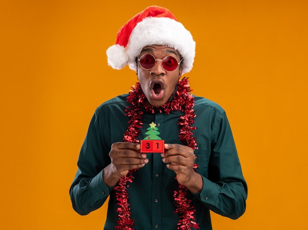 Uomo afroamericano in cappello della santa con la ghirlanda che indossa gli occhiali da sole che tengono i cubi del giocattolo con la data del nuovo anno che guarda l'obbiettivo stupito e scioccato in piedi sopra priorità bassa arancione