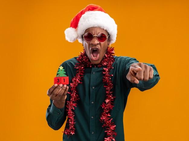 Uomo afroamericano in cappello della santa con la ghirlanda che indossa gli occhiali da sole che tengono i cubi del giocattolo con la data del nuovo anno che grida con l'espressione aggressiva che indica con la condizione del dito indice