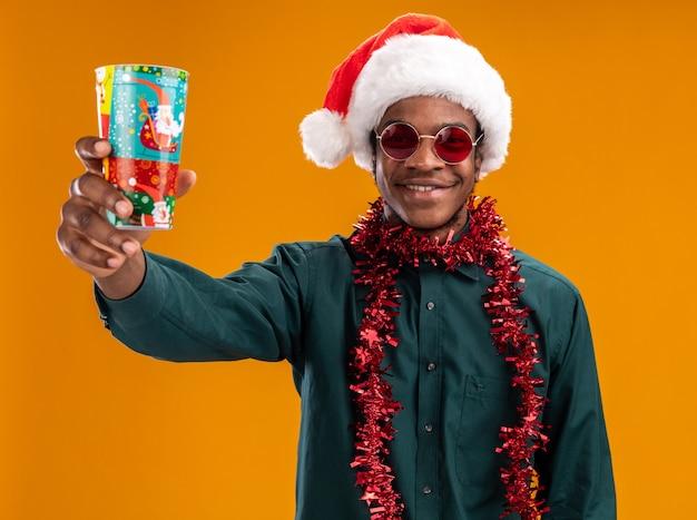 Uomo afroamericano in cappello della santa con la ghirlanda che indossa gli occhiali da sole che mostrano la tazza di carta variopinta che sorride allegramente in piedi sopra la parete arancione