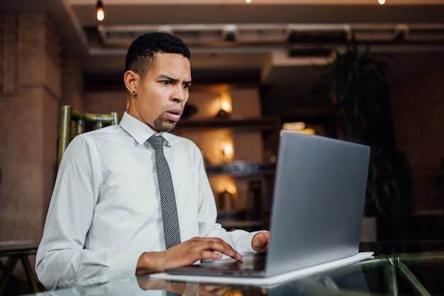 아프리카 계 미국인 남자는 흰색 셔츠, 실내에서 자신의 노트북에서 보는 것에 심각하게 놀랐습니다.