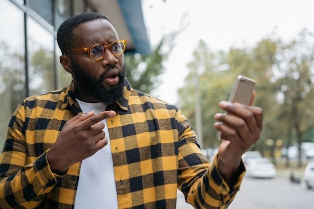Афро-американский мужчина делает покупки в интернете, указывая пальцем на мобильный телефон