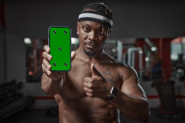 Афро-американский мужчина показывает телефон с зеленым экраном с точками отслеживания, тренировкой в тренажерном зале и спортивным приложением для