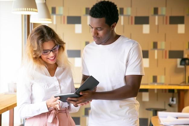 金髪の女性に新しいデザインを示すアフリカ系アメリカ人の男性