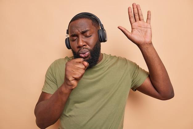 アフリカ系アメリカ人の男性が歌を歌い、マイクがプレーヤーからの音楽を聴いているかのように手を口の近くに保ちますワイヤレスヘッドフォンを使用しますカジュアルなtシャツを着ていますベージュの壁に隔離された暇な時間に楽しんでください