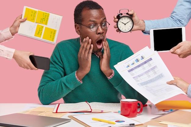 가제트와 서류로 둘러싸인 책상에 앉아 아프리카 계 미국인 남자