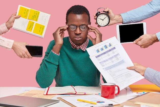 Uomo afroamericano seduto alla scrivania circondato da gadget e documenti