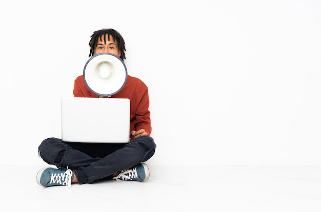 African american man sitting on the floor holding a computer