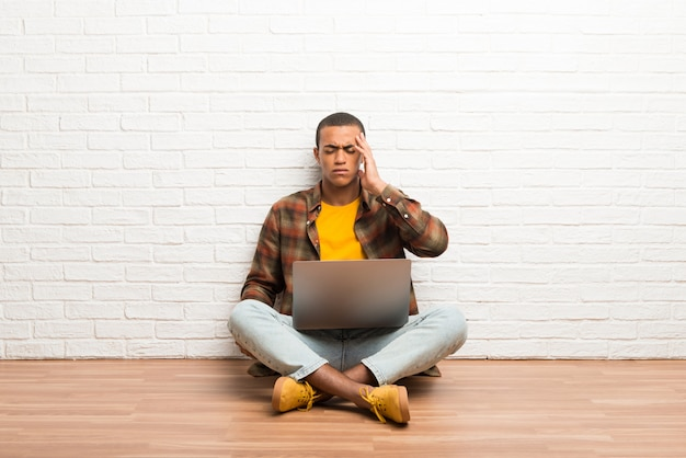 African american man sitting on the floor with his laptop unhappy and frustrated with something