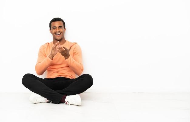 회의에서 발표한 후 박수를 치는 외진 카피스페이스 배경 위에 바닥에 앉아 있는 아프리카계 미국인 남자