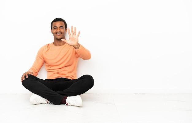 Афро-американский мужчина сидит на полу на изолированном фоне copyspace, считая пять пальцами