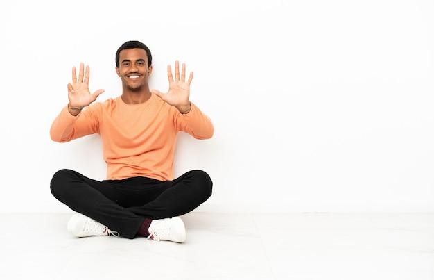 Афро-американский мужчина сидит на полу на изолированном фоне copyspace, считая девять пальцами