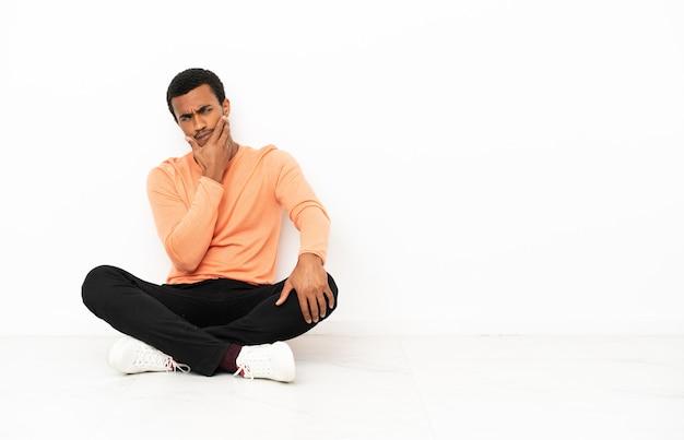 Афро-американский мужчина сидит на полу на изолированном фоне copyspace с сомнениями и смущенным выражением лица