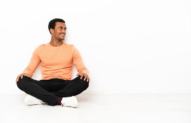 Афро-американский мужчина сидит на полу на изолированном фоне copyspace в боковом положении