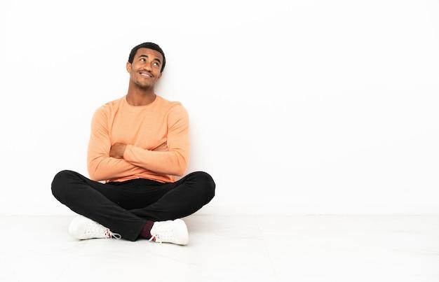 Афро-американский мужчина сидит на полу на изолированном фоне copyspace, глядя вверх, улыбаясь