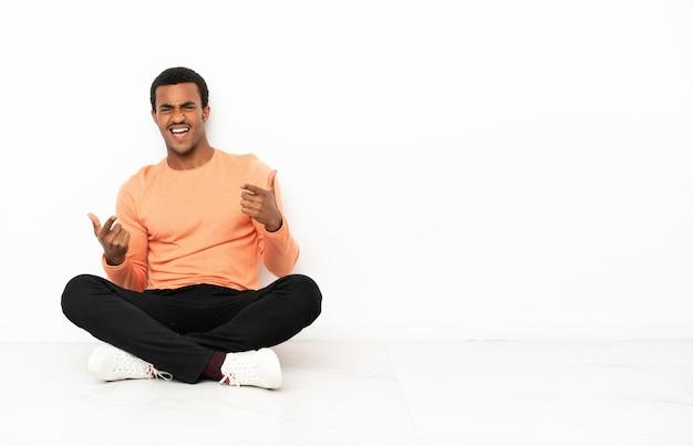 Афро-американский мужчина сидит на полу на изолированном фоне copyspace, указывая на фронт и улыбаясь