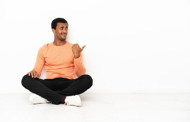 Афро-американский мужчина сидит на полу на изолированном фоне copyspace, указывая в сторону, чтобы представить продукт