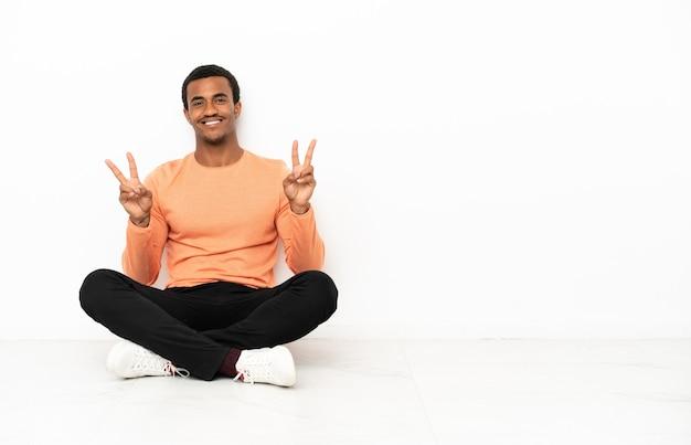 Афро-американский мужчина сидит на полу на изолированном фоне copyspace, показывая знак победы обеими руками