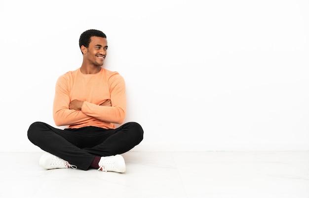 Афро-американский мужчина сидит на полу на изолированном фоне copyspace со скрещенными руками и счастлив