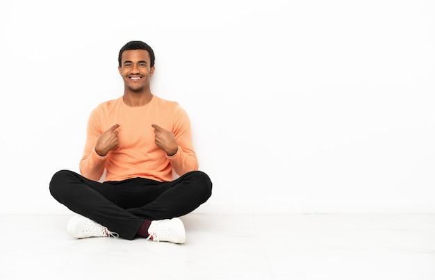 Афро-американский мужчина сидит на полу на изолированном фоне copyspace с удивленным выражением лица